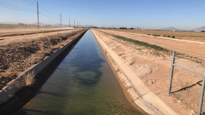 A canal carries water to farms and homes outside of Maricopa on Dec. 19, 2018.