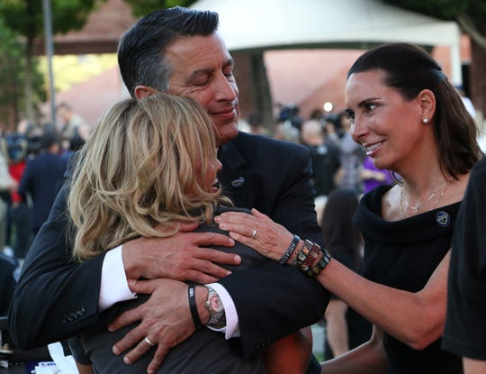 Nevada Governor Brian Sandoval and his wife Lauralyn McCarthy comfort Mynda Smith during the 1 October Sunrise Remembrance at the Clark County Government Center Amphitheater in Las Vegas on Oct. 1, 2018.  The ceremony marked the one year anniversary of the mass shooting in Las Vegas.