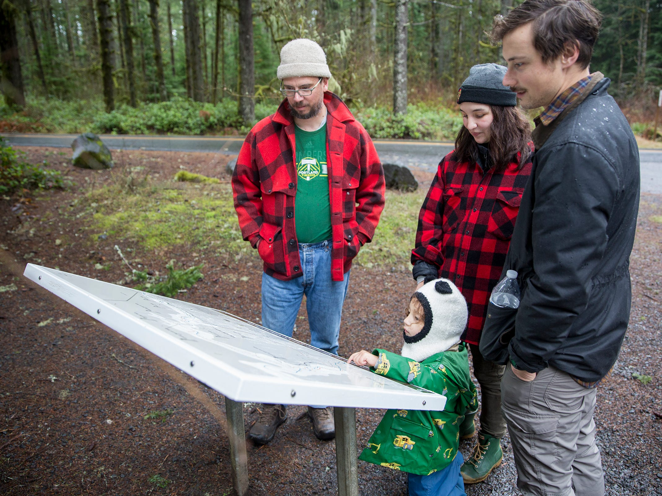 Ynez Basurta, Jeremy Basurto, their three-year-old son Ozzie and Joe Lopez look over the South Silver Falls map at Silver Falls State Park in Sublimity on Wednesday, Dec. 26, 2018. The family said they were working off Christmas cookies.