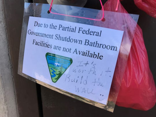 A sign regarding the partial federal government shutdown is hung on a restroom door at Fort Ord National Monument.