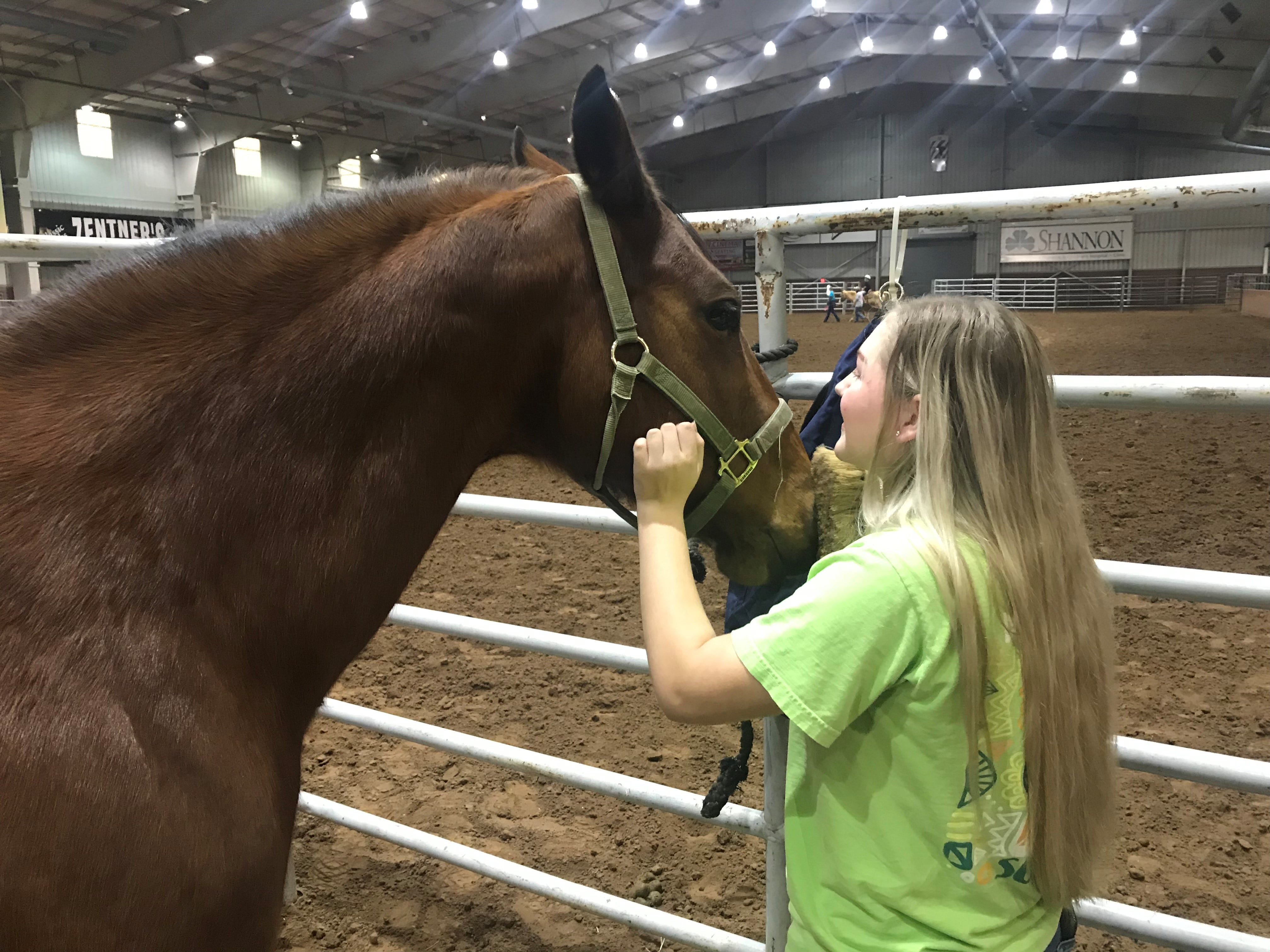 Jacey Brashear brushes her horse Faith on Dec. 25, 2018 during the Hope, Love and Horses event hosted by Sonrisas Trails and Stone Arbor Farms at 1st Community Federal Credit Union Spur Arena.