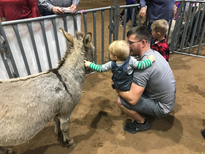 John Anderson holds his son Jacob while he pets a donkey Dec. 25, 2018 during the Hope, Love and Horses event hosted by Sonrisas Trails and Stone Arbor Farms at 1st Community Federal Credit Union Spur Arena.