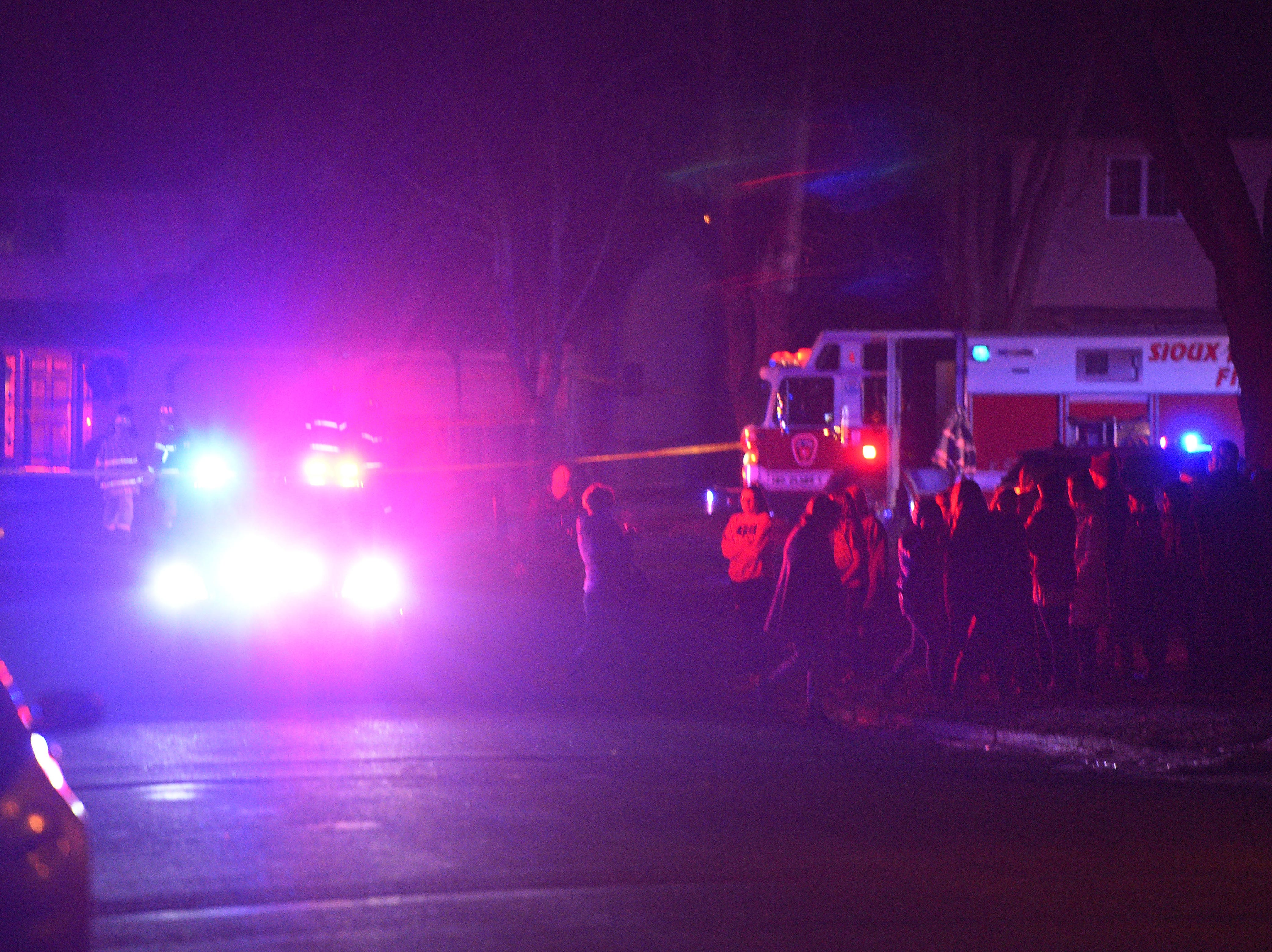 Onlookers at told to move back after firefighters begin looking for debris after a plane crashed into a home in the 4200 block of south Birchwood Avenue Tuesday, Dec. 25, in Sioux Falls.