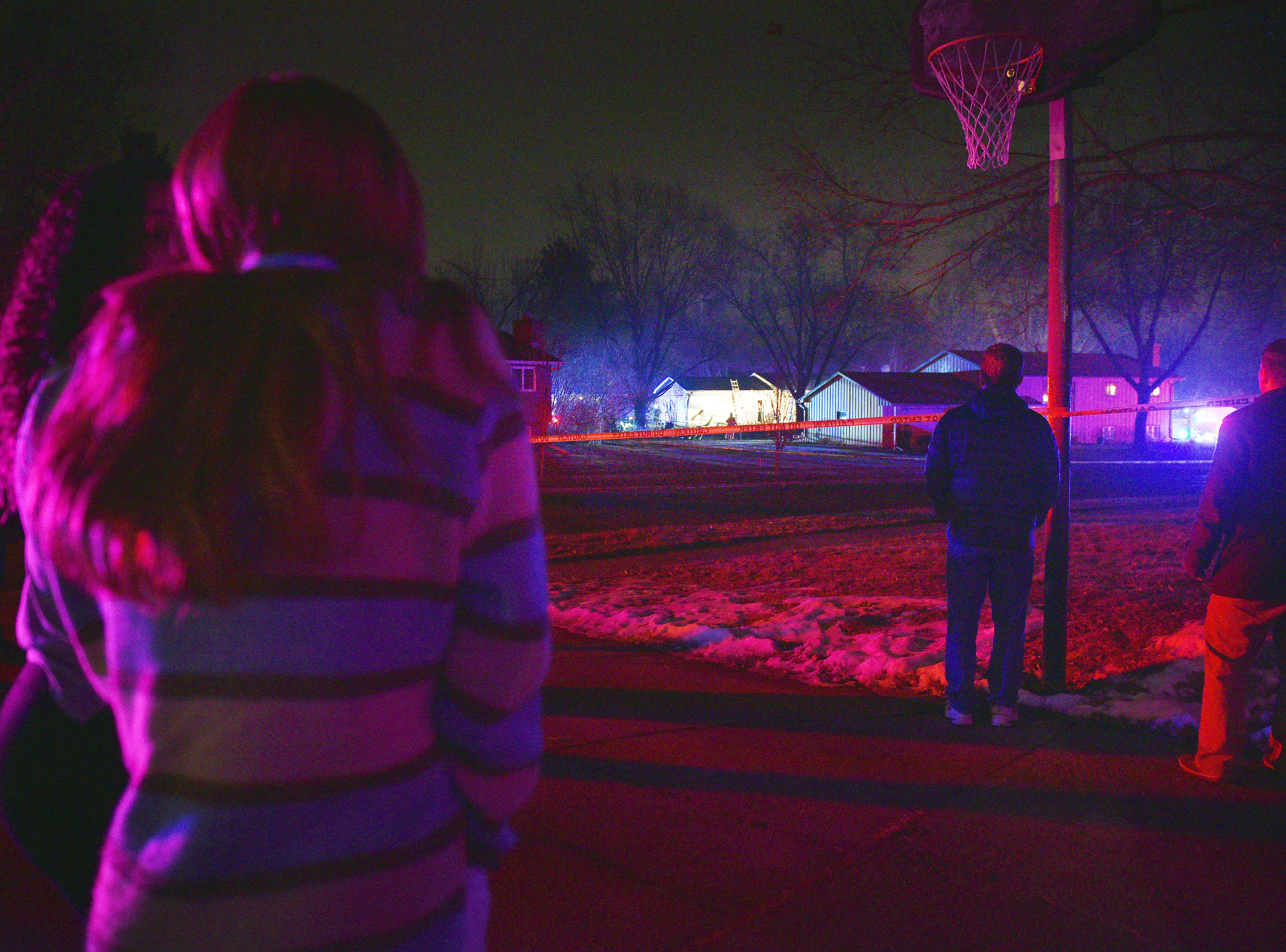 Neighbors stand behind caution tape as they watch firefighters look for debris after a plane crashed into a home in the 4200 block of south Birchwood Avenue Tuesday, Dec. 25, in Sioux Falls.