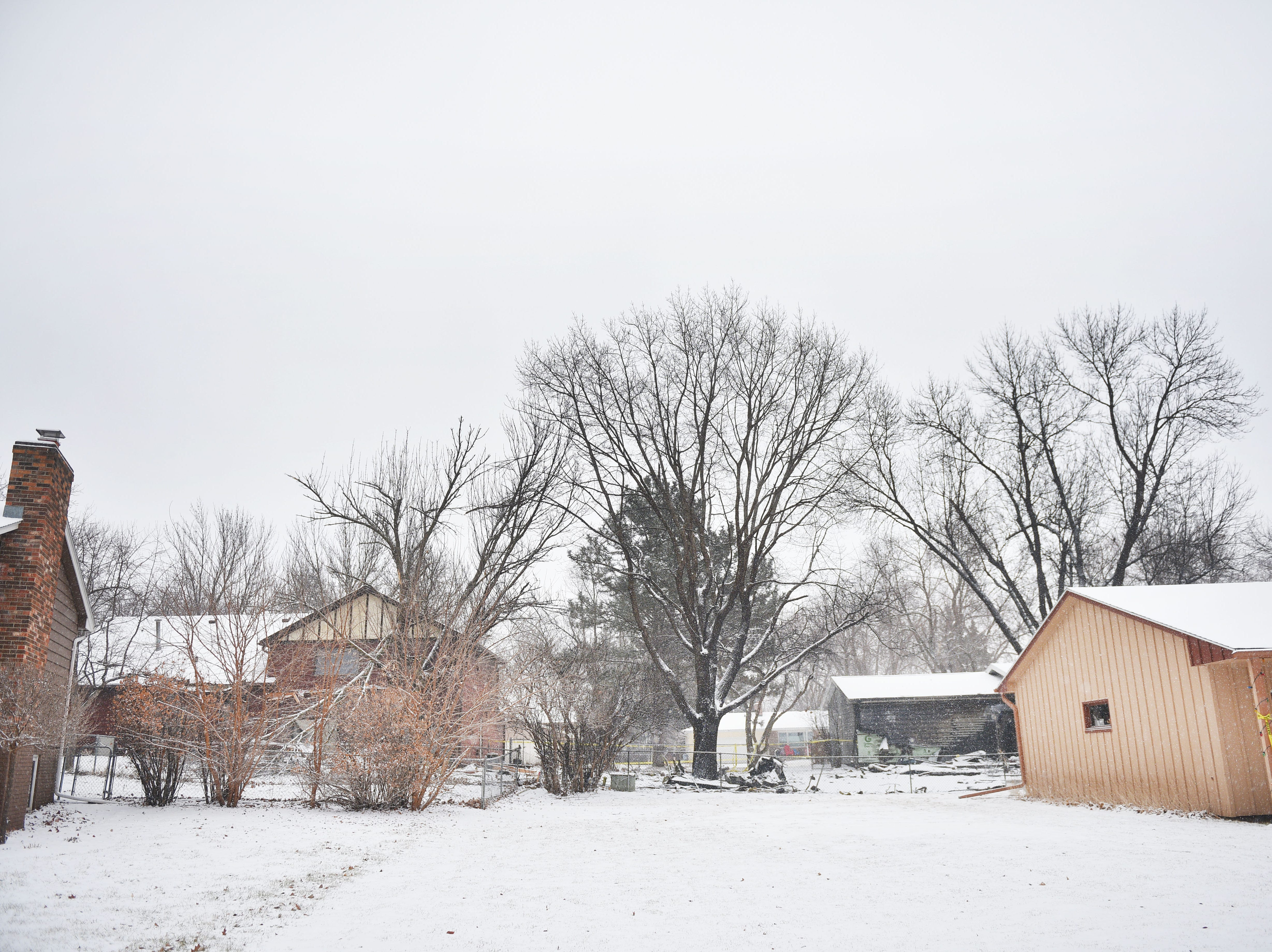 Broken trees and debris are visible at the 4200 block of south Birchwood Avenue after a plane crashed into the neighborhood Wednesday, Dec. 26, in Sioux Falls.