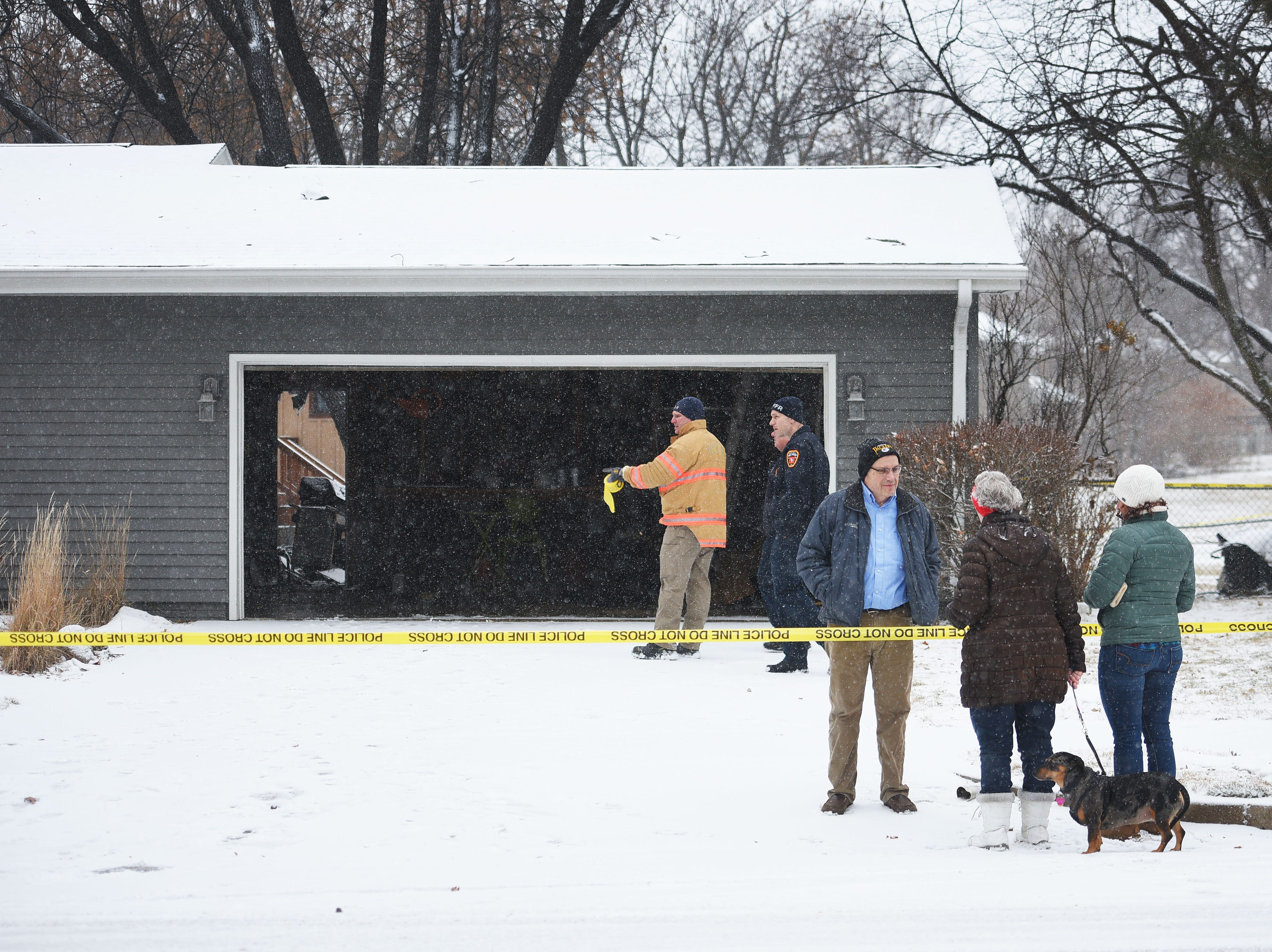 Tim Brodkorb, bottom right, talks to neighbors while police and fire check his garage at 4213 S Birchwood Wednesday, Dec. 26, in Sioux Falls. Pat and Tim Brodkorb were the first who were allowed to return home after evacuating their home last night after a plane crashed into their backyard.