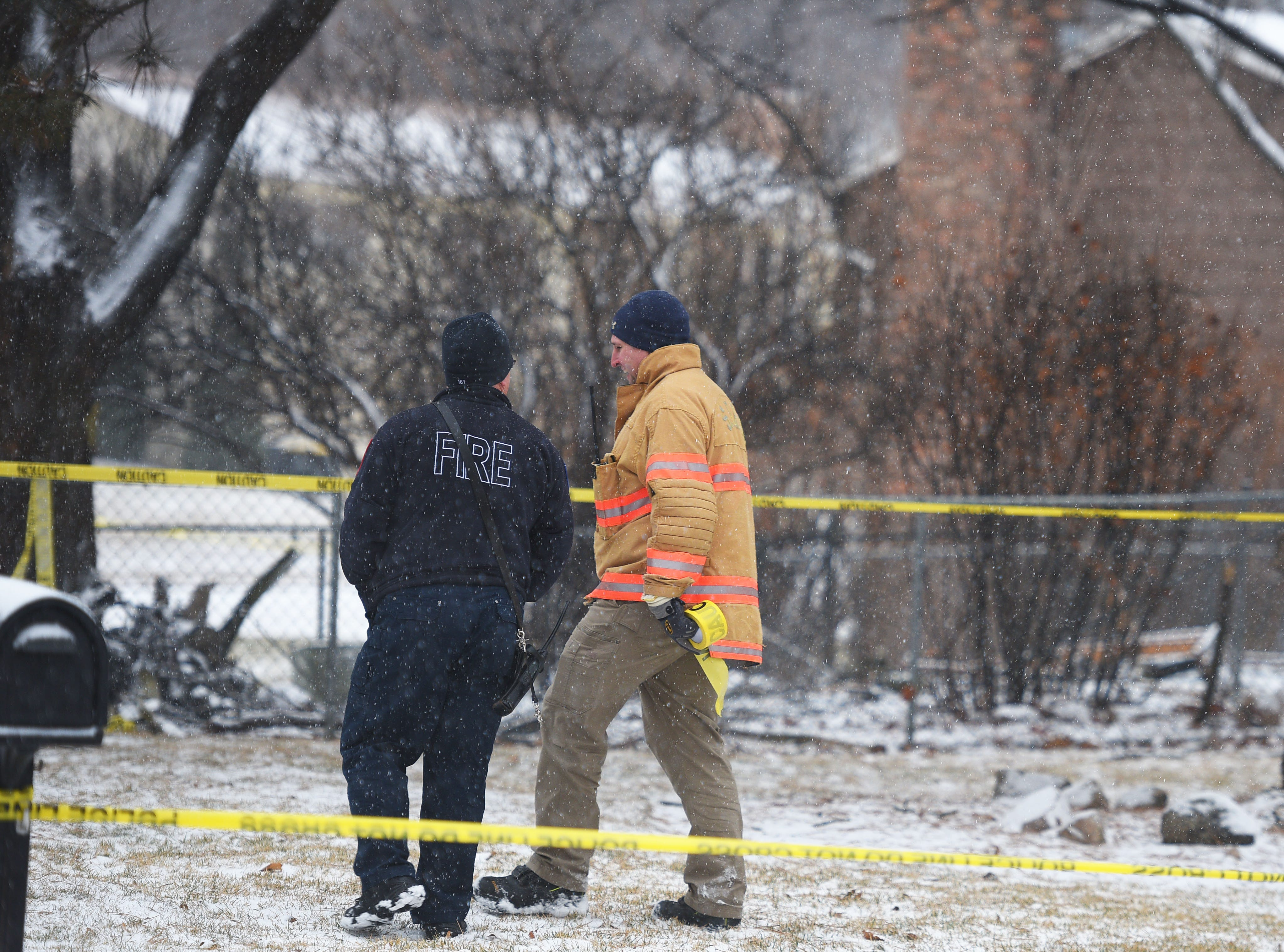 Fire and police monitor the home of Pat and Tim Brodkorb at 4213 S Birchwood Wednesday, Dec. 26, in Sioux Falls. A plane crashed into their backyard Tuesday night. The crash caused the back of their home to catch fire. Nearby homes were still evacuated.