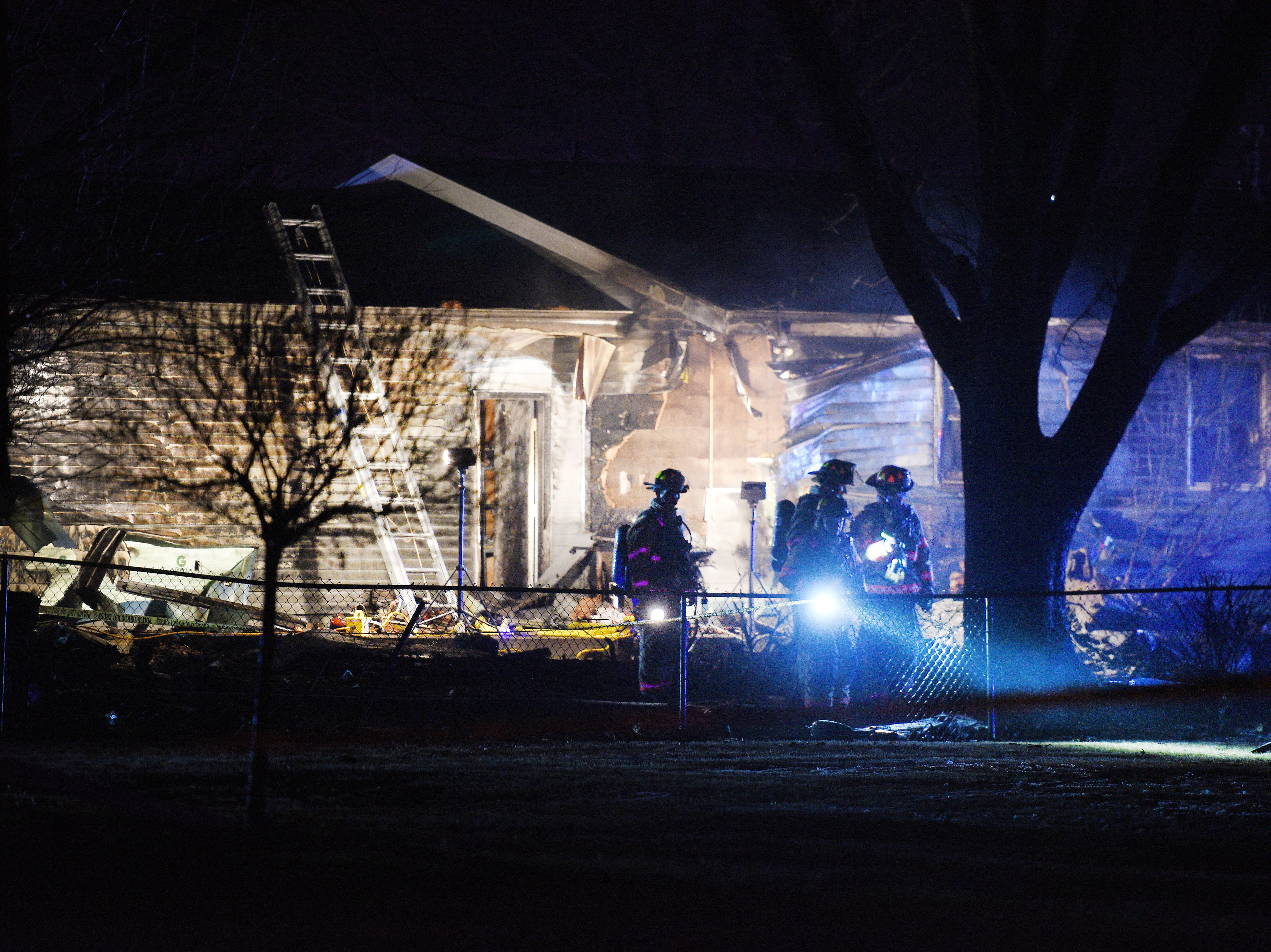Firefighters use flash lights to search the area for debris after a plane crashed into a home in the 4200 block of south Birchwood Avenue Tuesday, Dec. 25, in Sioux Falls.