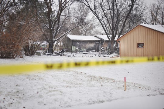 Caution tape is used to contain areas where there is debris from a plane that crashed into a home at the 4200 block of south Birchwood Avenue Wednesday, Dec. 26, in Sioux Falls.