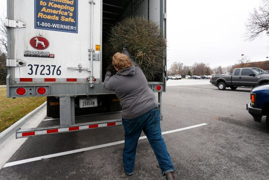 Boy Scout Greg Doermer tosses a Christmas tree into a trailer at the annual Christmas tree recycling program in the parking lot of Bass Pro Shops on Wednesday, Dec. 26, 2018.