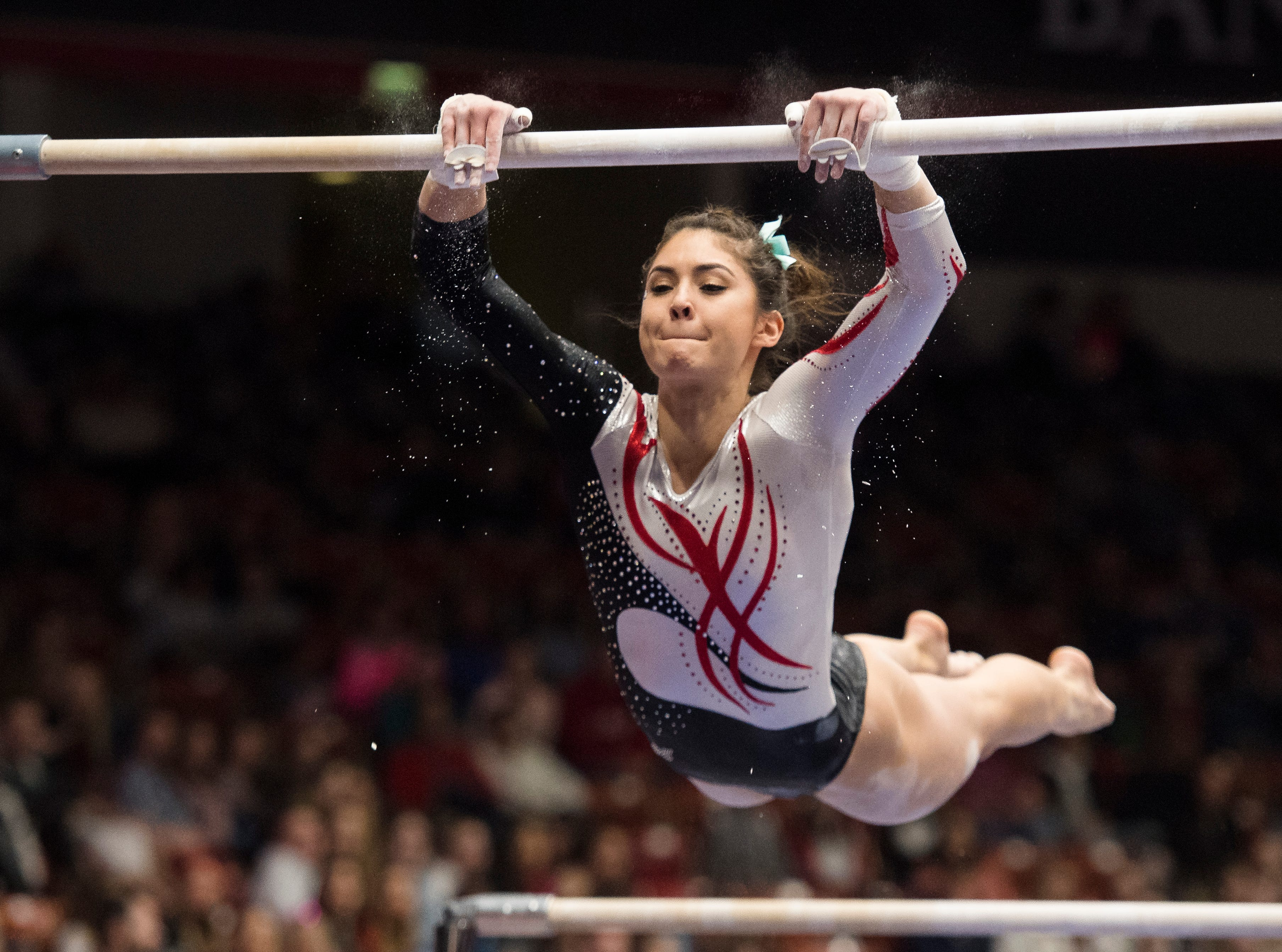 Southern Utah University senior Karen Gonzalez leaps onto the bar during her double bar performance against University of Washington at the America First Event Center Saturday, March 3, 2018.