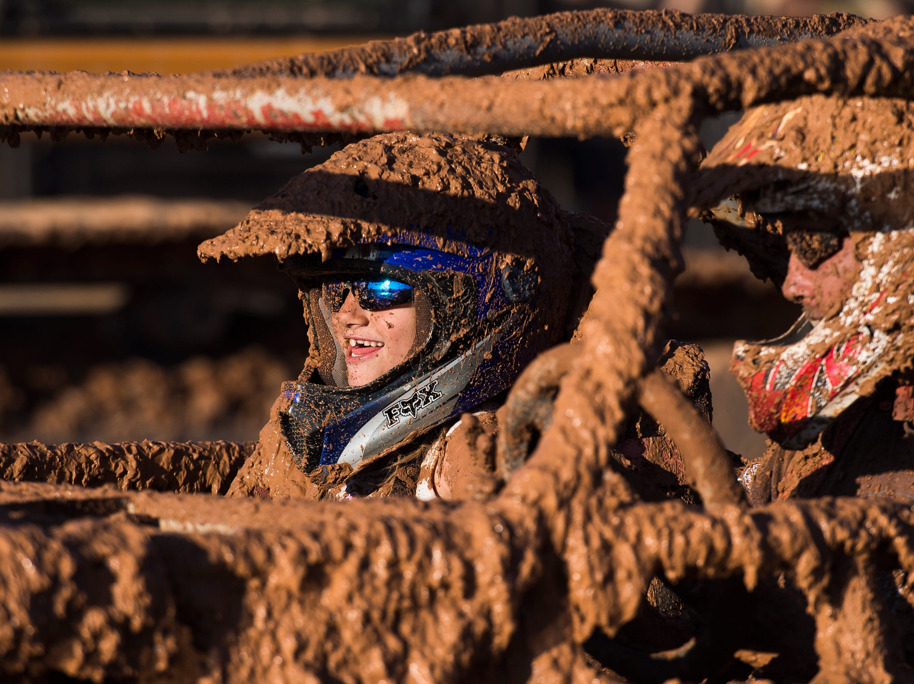 A mud-covered child laughs after a run in the Iron County Fair's Mud Bog at Parowan Saturday, August 18, 2018.