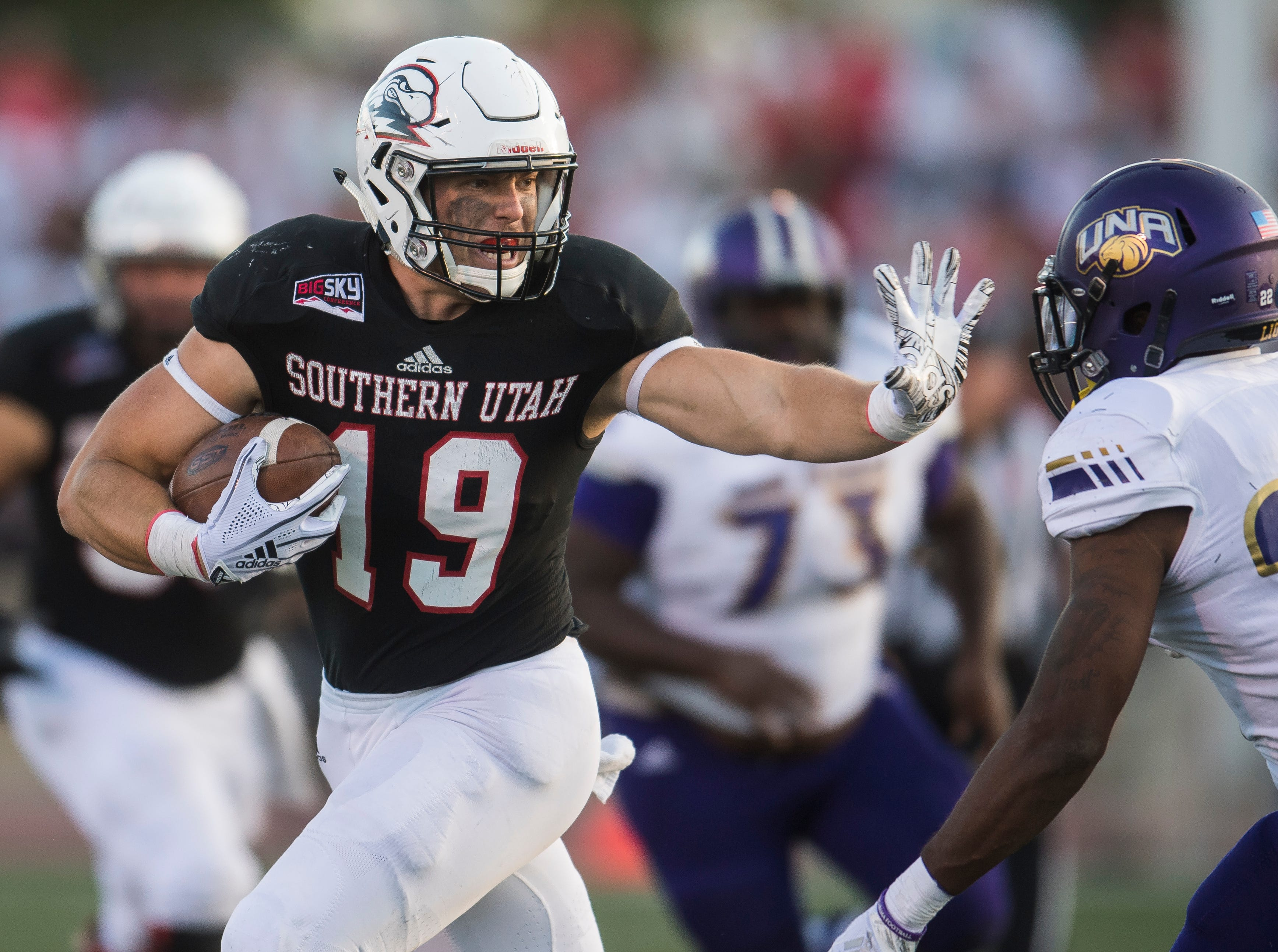Southern Utah University tight end Logan Parker (19) stiff arms his opponent against North Alabama University at Eccles Coliseum  Saturday, September 1, 2018.