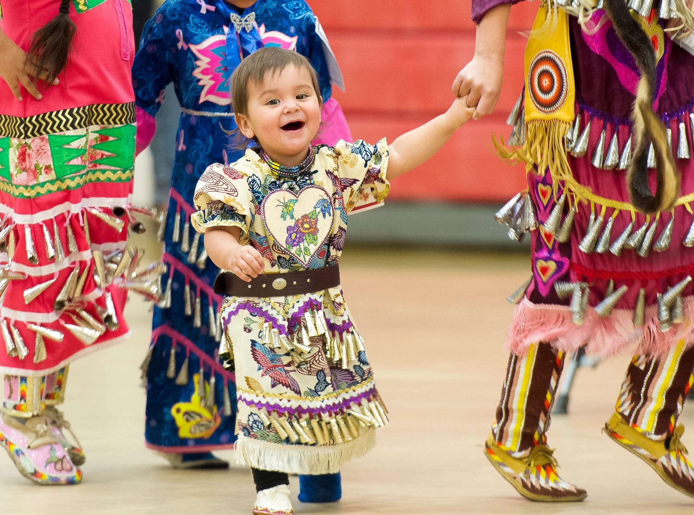 Gracie Leslie, 18 months, laughs while dancing with her family at the Native American powwow at the Paiute Tribal Clinic Friday, March 30, 2018.