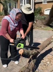 FSU alumna Iman Zawahry helps cut a fallen tree with a chainsaw in her hometown of Panama City ravaged from Hurricane Michael.