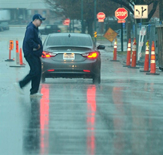A pedestrian crosses a rain wet street in downtown Wichita Falls as most of the Wichita Falls area saw periods of heavy rain, wind, and lightning, Wednesday morning.