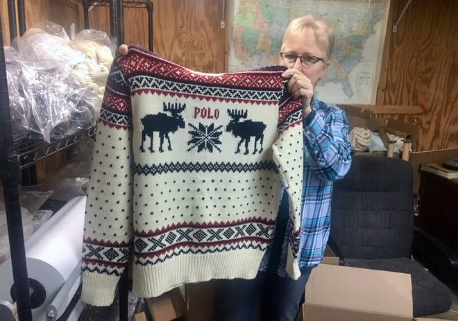 This Oct. 16, 2018 photo shows Debbie McDermott holding up the front side of a Ralph Lauren sweater in East Jordan, Mich., that athletes wore for the 2014 Winter Olympics closing ceremony. The sweater was made using Shepherd's Wool, one of Stonehedge Fiber Mill's yarn lines.