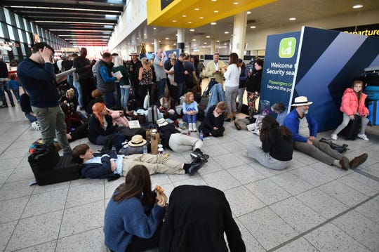 Passengers wait at the North Terminal at London Gatwick Airport, south of London, on December 20, 2018 after all flights were grounded due to drones flying over the airfield.