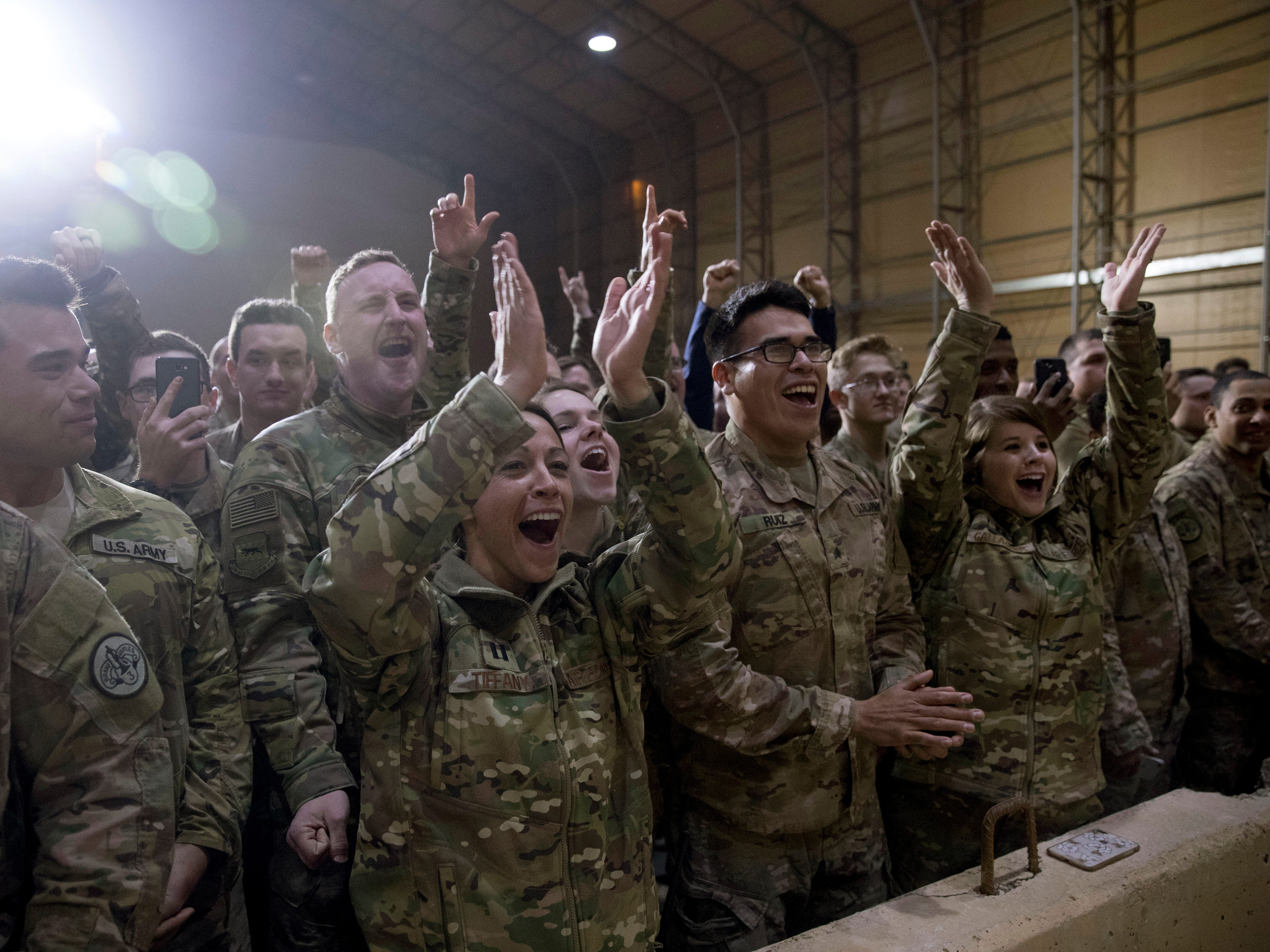 Members of the military cheer as President Donald Trump speaks at a hanger rally at Al Asad Air Base, Iraq, Wednesday, Dec. 26, 2018. President Donald Trump, who is visiting Iraq, says he has 'no plans at all' to remove US troops from the country.  (AP Photo/Andrew Harnik) ORG XMIT: IRQA201