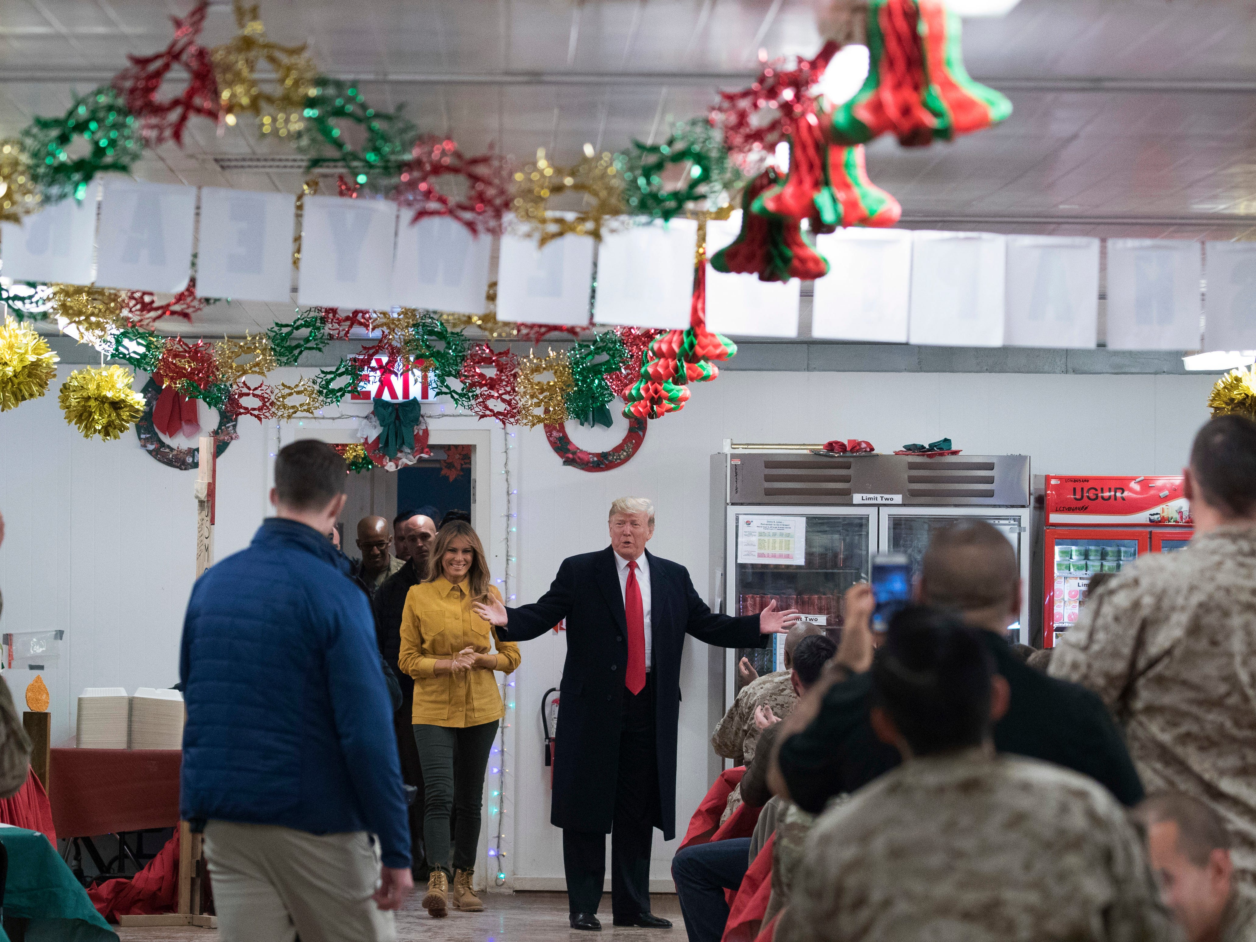 President Donald Trump and first lady Melania Trump arrive to visit with members of the military at a dining hall at Al Asad Air Base, Iraq, Wednesday, Dec. 26, 2018. (AP Photo/Andrew Harnik) ORG XMIT: IRQA108