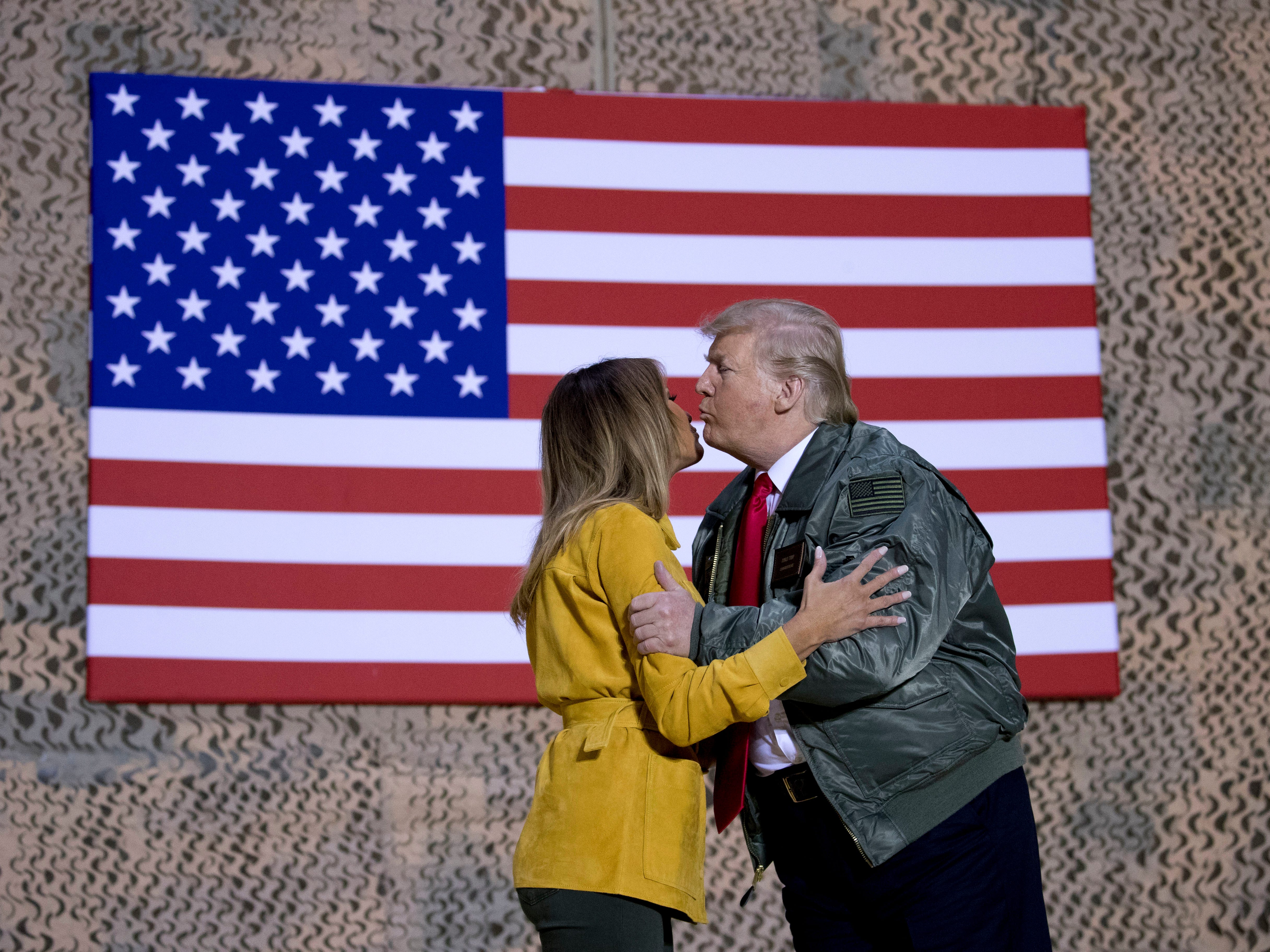 President Donald Trump kisses first lady Melania Trump during a hanger rally at Al Asad Air Base, Iraq, Wednesday, Dec. 26, 2018. President Donald Trump, who is visiting Iraq, says he has 'no plans at all' to remove US troops from the country. (AP Photo/Andrew Harnik) ORG XMIT: IRQA202