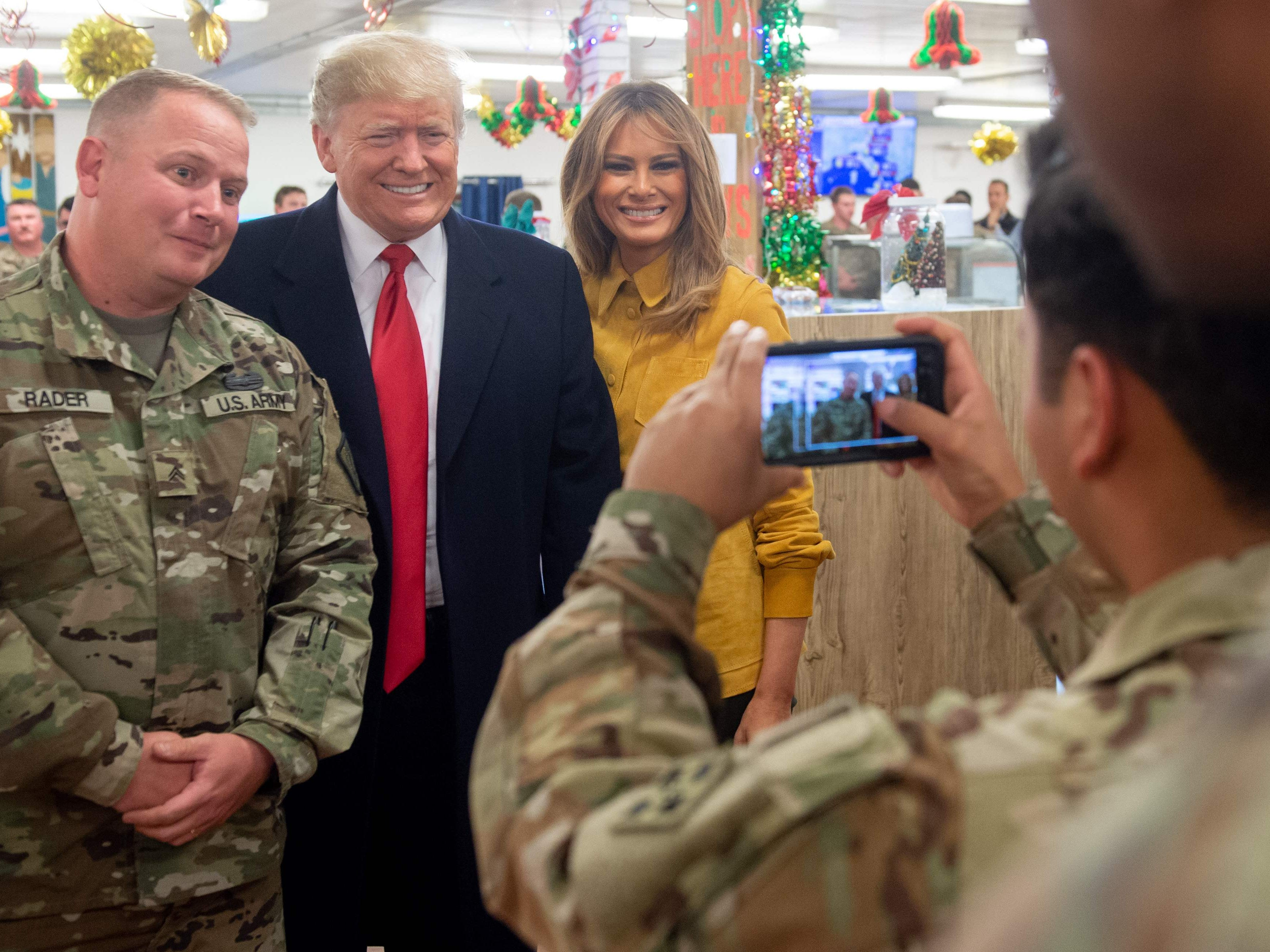 US President Donald Trump and First Lady Melania Trump take photos with members of the US military during an unannounced trip to Al Asad Air Base in Iraq on December 26, 2018. - President Donald Trump arrived in Iraq on his first visit to US troops deployed in a war zone since his election two years ago (Photo by SAUL LOEB / AFP)SAUL LOEB/AFP/Getty Images ORG XMIT: US Presid ORIG FILE ID: AFP_1BU3JR