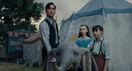 "Former circus star Holt Farrier (Colin Farrell, left) and his children Milly (Nico Parker) and Joe (Finley Hobbins) care for a very special newborn elephant in Tim Burton's ""Dumbo."""