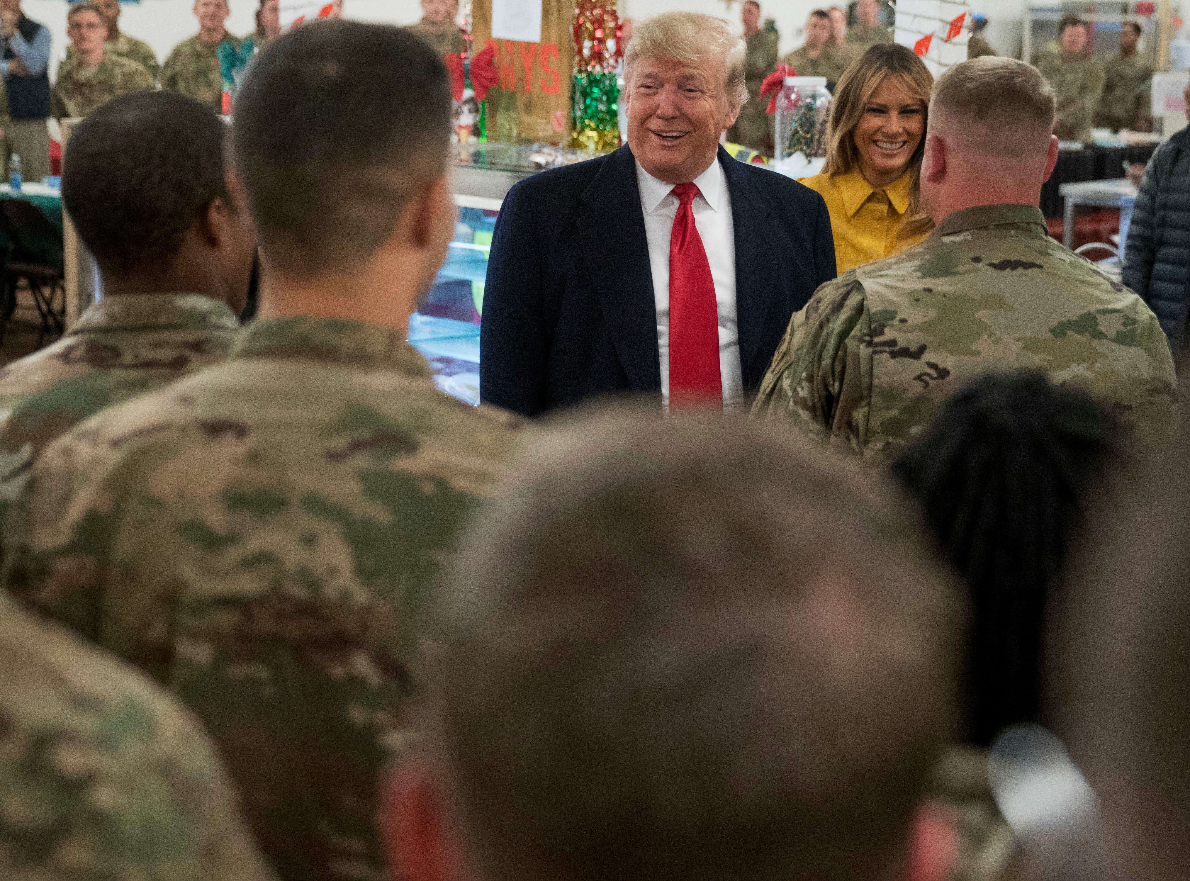 President Donald Trump and first lady Melania Trump visit with members of the military at a dining hall at Al Asad Air Base, Iraq, Wednesday, Dec. 26, 2018. (AP Photo/Andrew Harnik) ORG XMIT: IRQA132