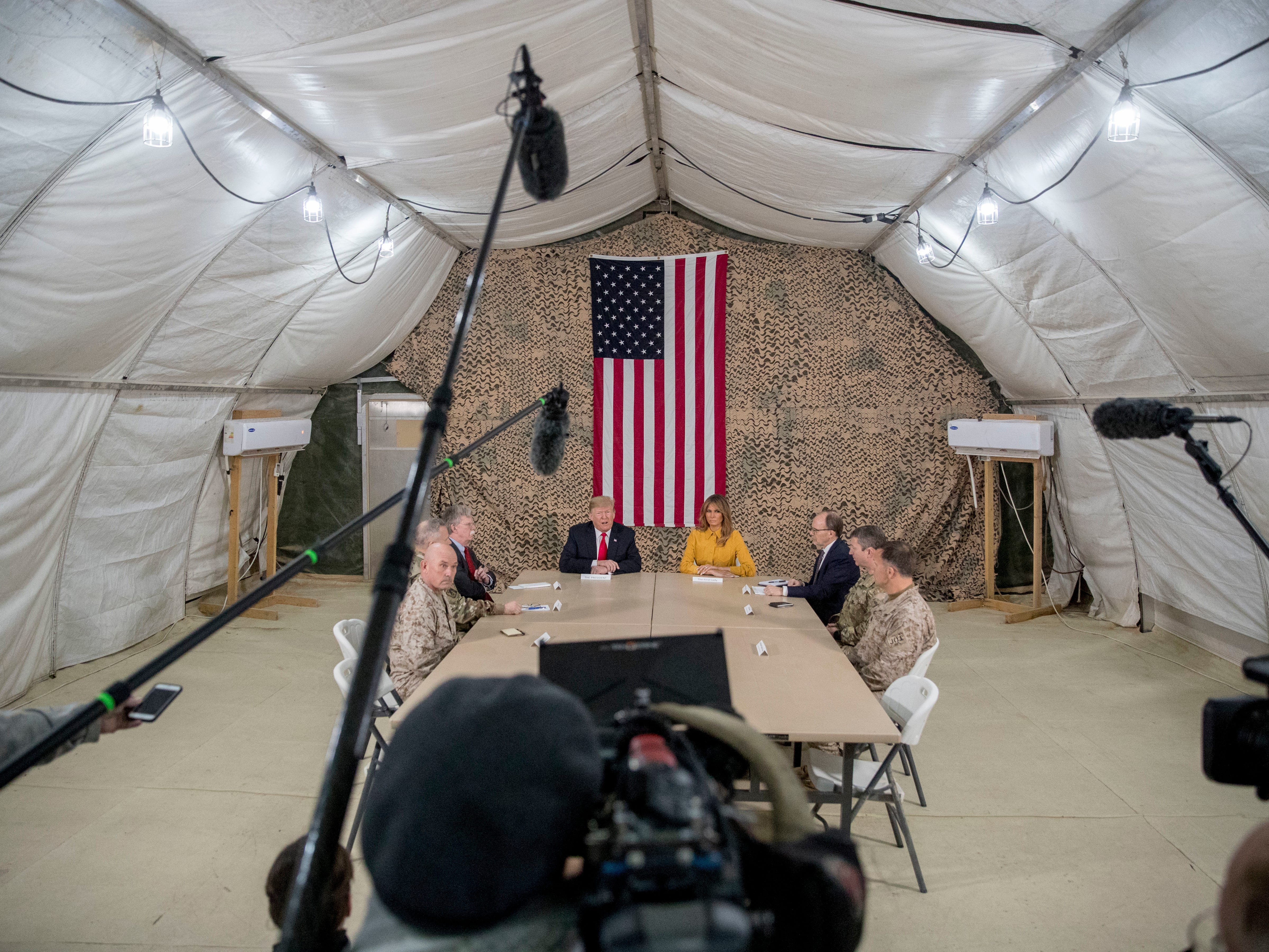President Donald Trump, accompanied by National Security Adviser John Bolton, third from left, first lady Melania Trump, fourth from right, US Ambassador to Iraq Doug Silliman, third from right, and senior military leadership, speaks to members of the media at Al Asad Air Base, Iraq, Wednesday, Dec. 26, 2018. (AP Photo/Andrew Harnik) ORG XMIT: IRQA103