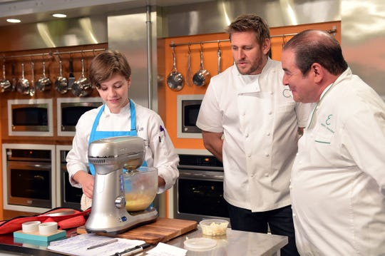 Nikki Bidun, left, the Season 2 winner of Universal Kids' 'Top Chef Junior,' prepares a meal as head judge Curtis Stone and guest judge Emeril Lagasse observe her work.