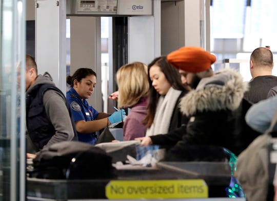 A Transportation Security Administration agent screens passengers at O'Hare International Airport, Tuesday, Dec. 25, 2018, in Chicago. Already crowded airports this week are expected to face weather related delays.