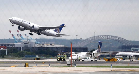 In this July 25, 2013 file photo, a United Airlines plane, top left, takes off from Newark Liberty International Airport, in Newark, New Jersey.