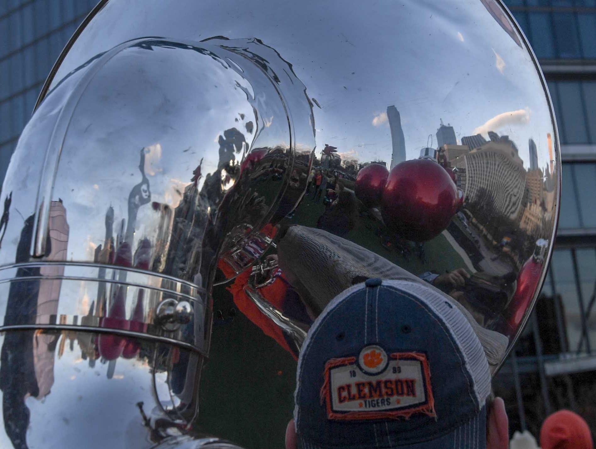 A skyline of downtown buildings reflect in a tuba during Clemson Band practice outside the Omni in Dallas December 27, 2018.