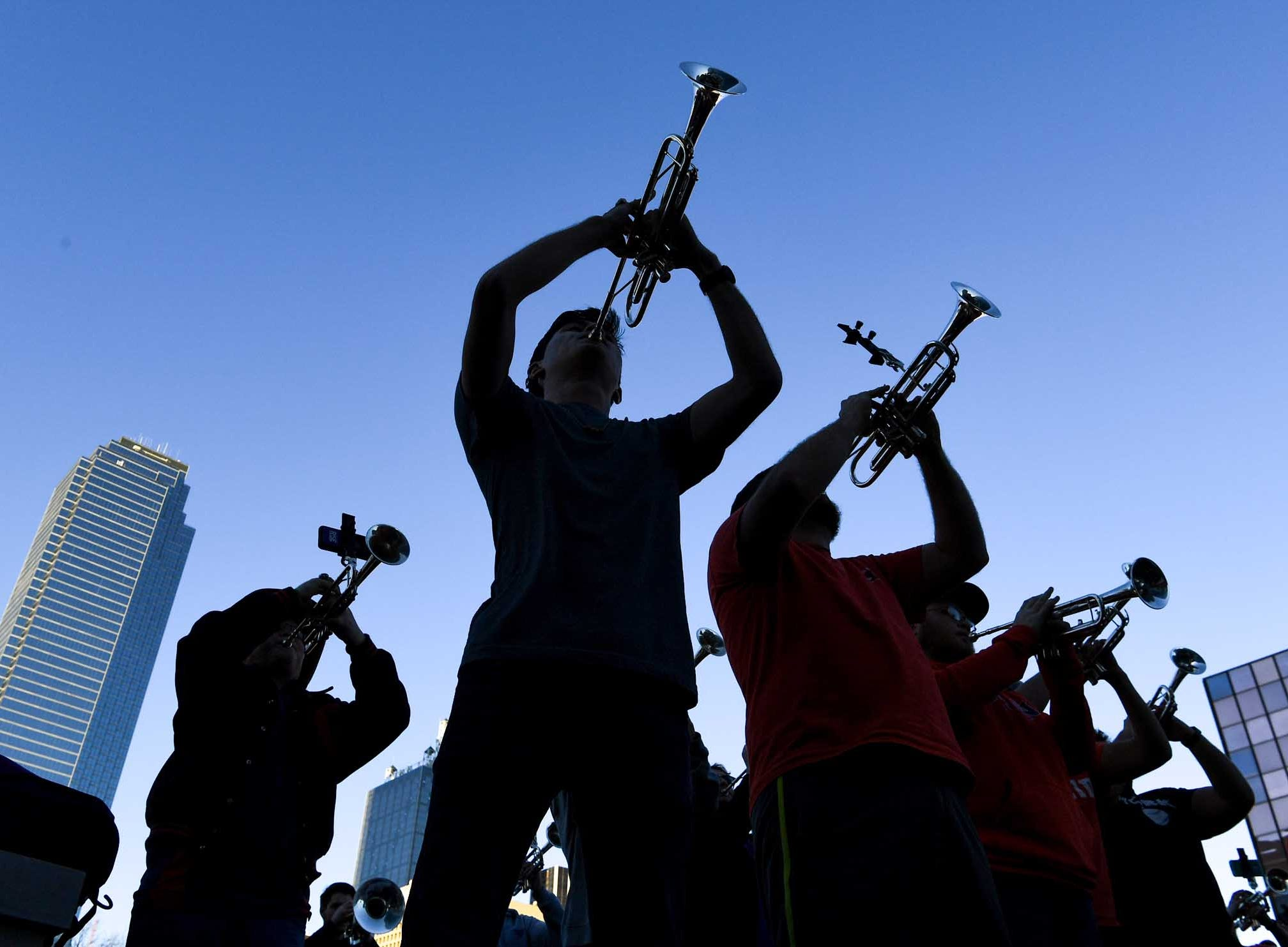 Will McAlhany plays trumpet with bandmates near a skyline of buildings during Clemson Band practice outside the Omni in downtown Dallas December 27, 2018.