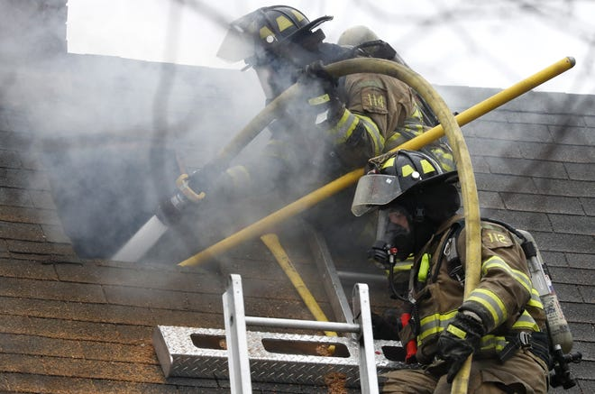 Firefighters work the scene of a fire Thursday on West 10th Street.