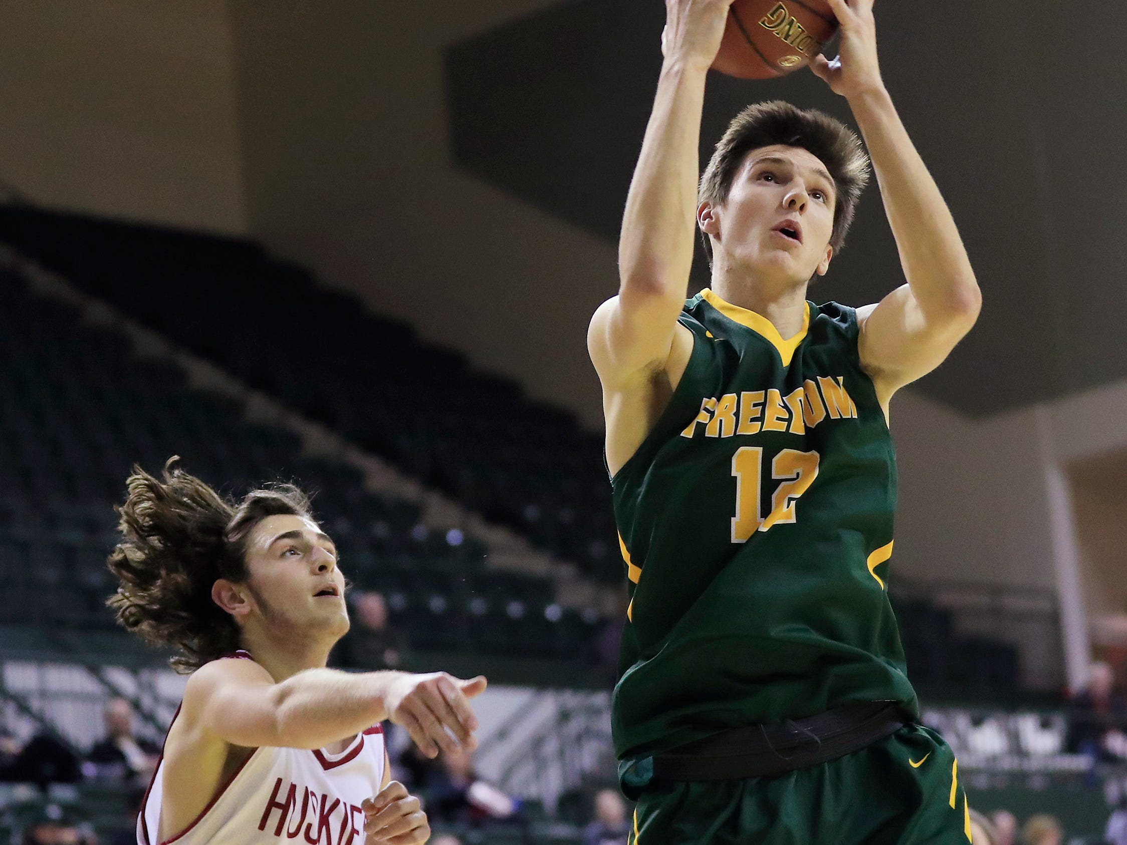 Freedom's Hunter Wiese (12) receives a ball in the paint against New Holstein's Owen Heus (21) at the Sun Drop Shootout at the Kress Center on Thursday, December 27, 2018 in Green Bay, Wis.