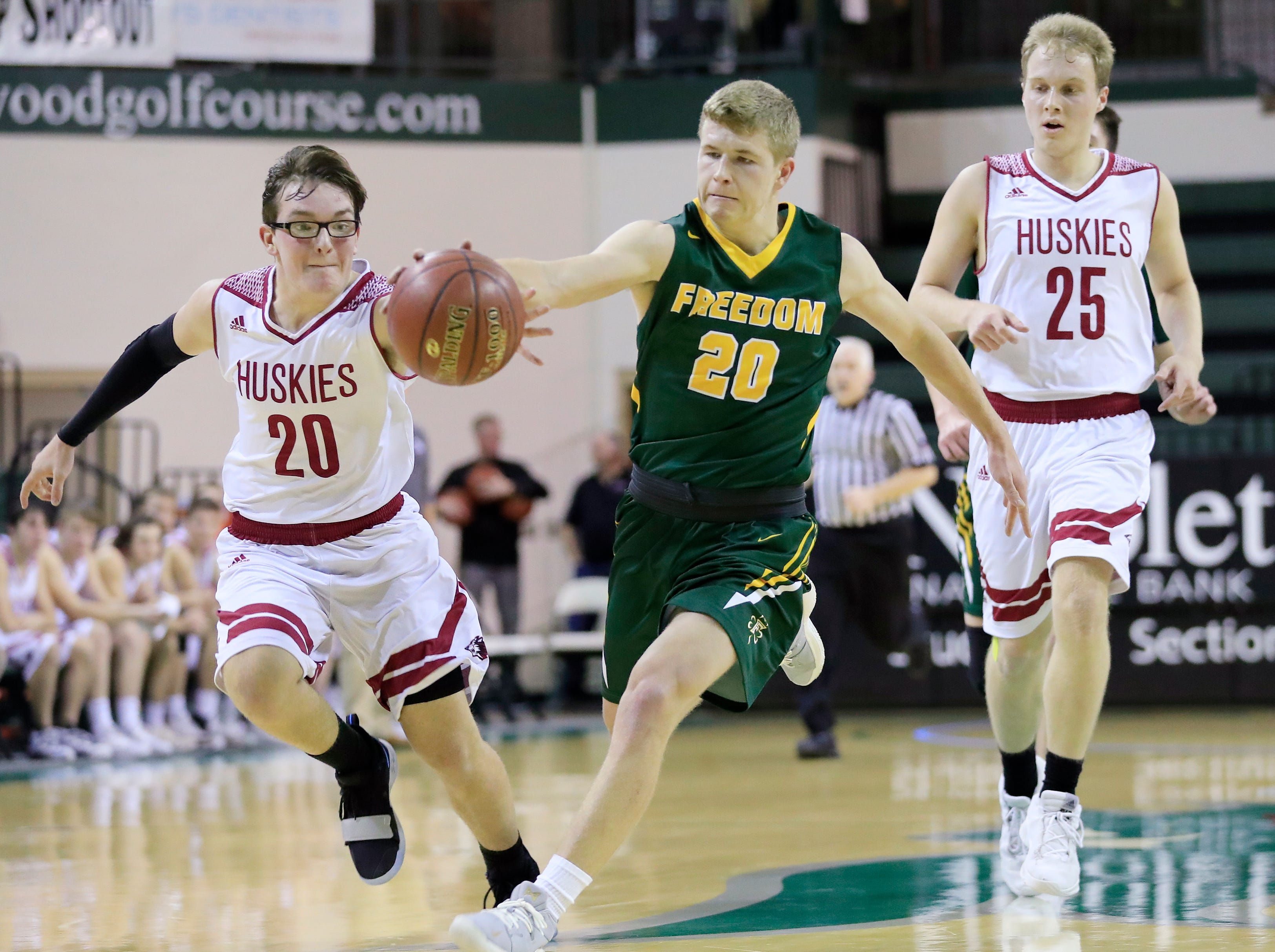 Freedom's Bryce Vandenberg (20) and New Holstein's Dayne Jacobson (20) compete for a loose ball at the Sun Drop Shootout at the Kress Center on Thursday, December 27, 2018 in Green Bay, Wis.