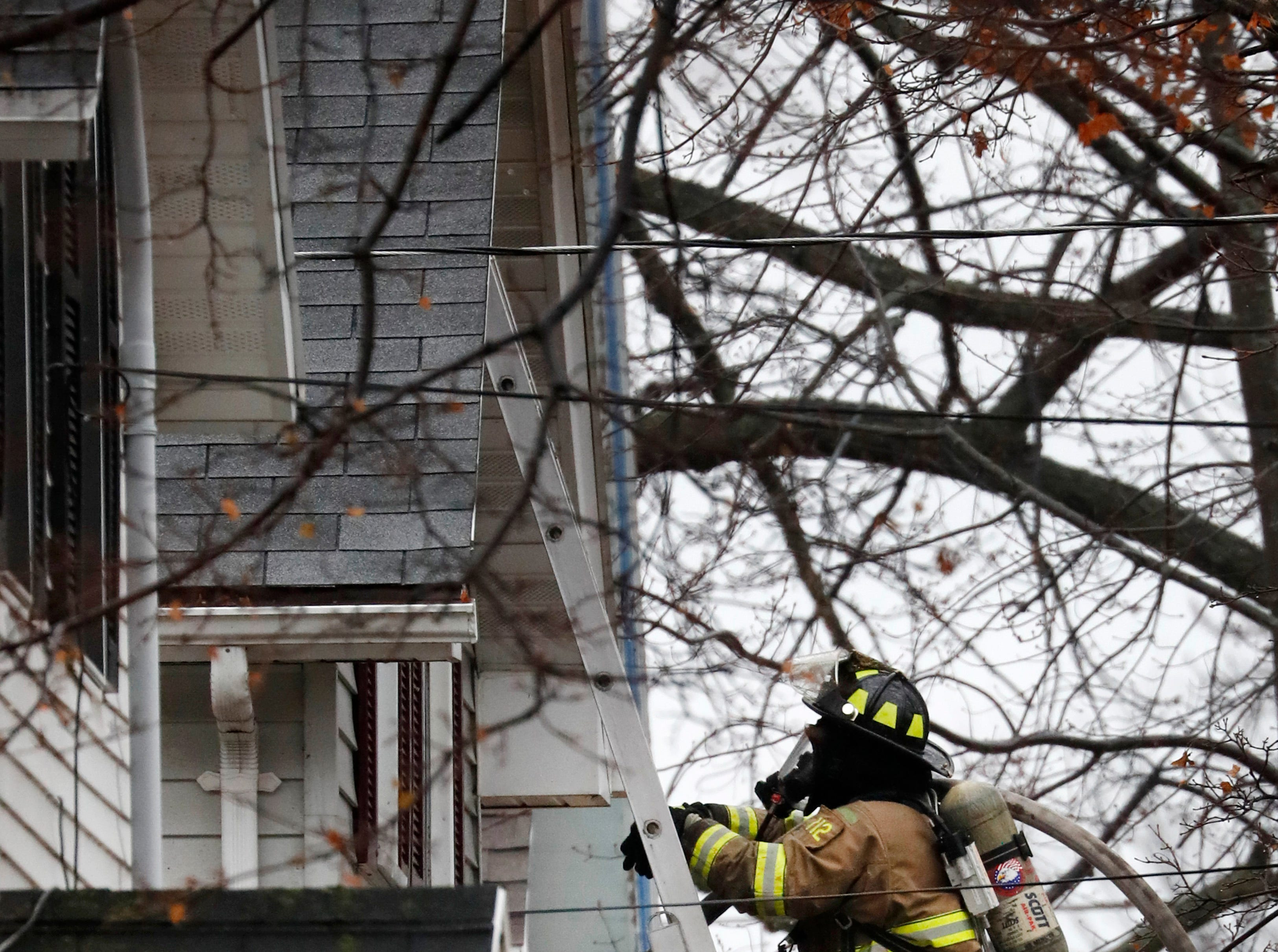 A Kaukauna firefighter climbs to the peak of a building while working to put out a structure fire on West 10th Street Thursday, Dec. 27, 2018, Kaukauna, Wis.