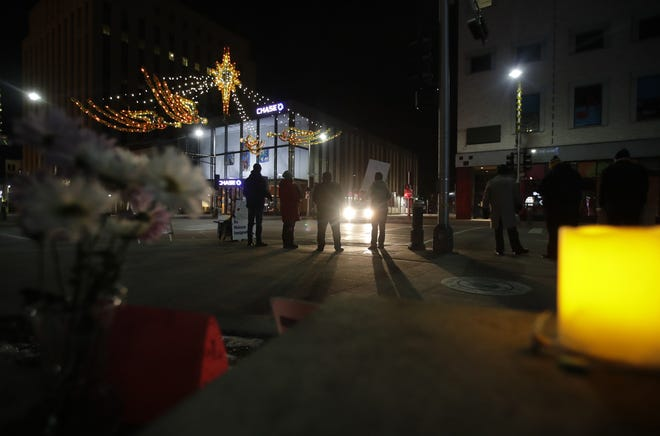 Protesters are lit by a car's headlights shortly after midnight on Christmas morning during the 24-hour Christmas in Tornillo: Fox Valley Vigil, which ran from noon on Christmas Eve to noon on Christmas Day. Marijke van Roojen, of the Winnebago Worship Group, and Marie Luna, director of congregational life at the Fox Valley Unitarian Universalist Fellowship, went to Tornillo, Texas. on the U.S. and Mexico border to protest the tent camp for migrant children.