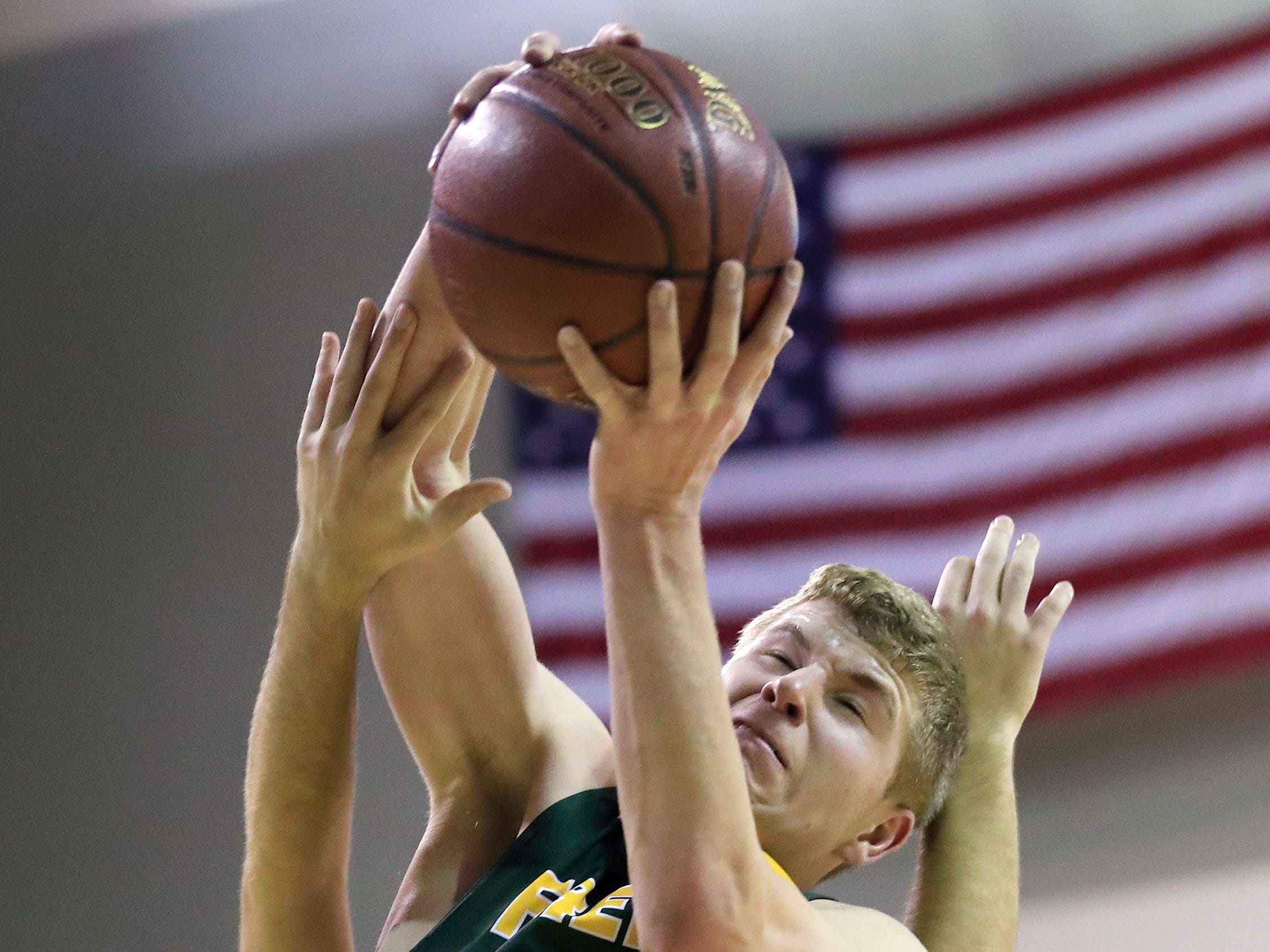 Freedom's Bryce Vandenberg (20) grabs a rebound against New Holstein at the Sun Drop Shootout at the Kress Center on Thursday, December 27, 2018 in Green Bay, Wis.