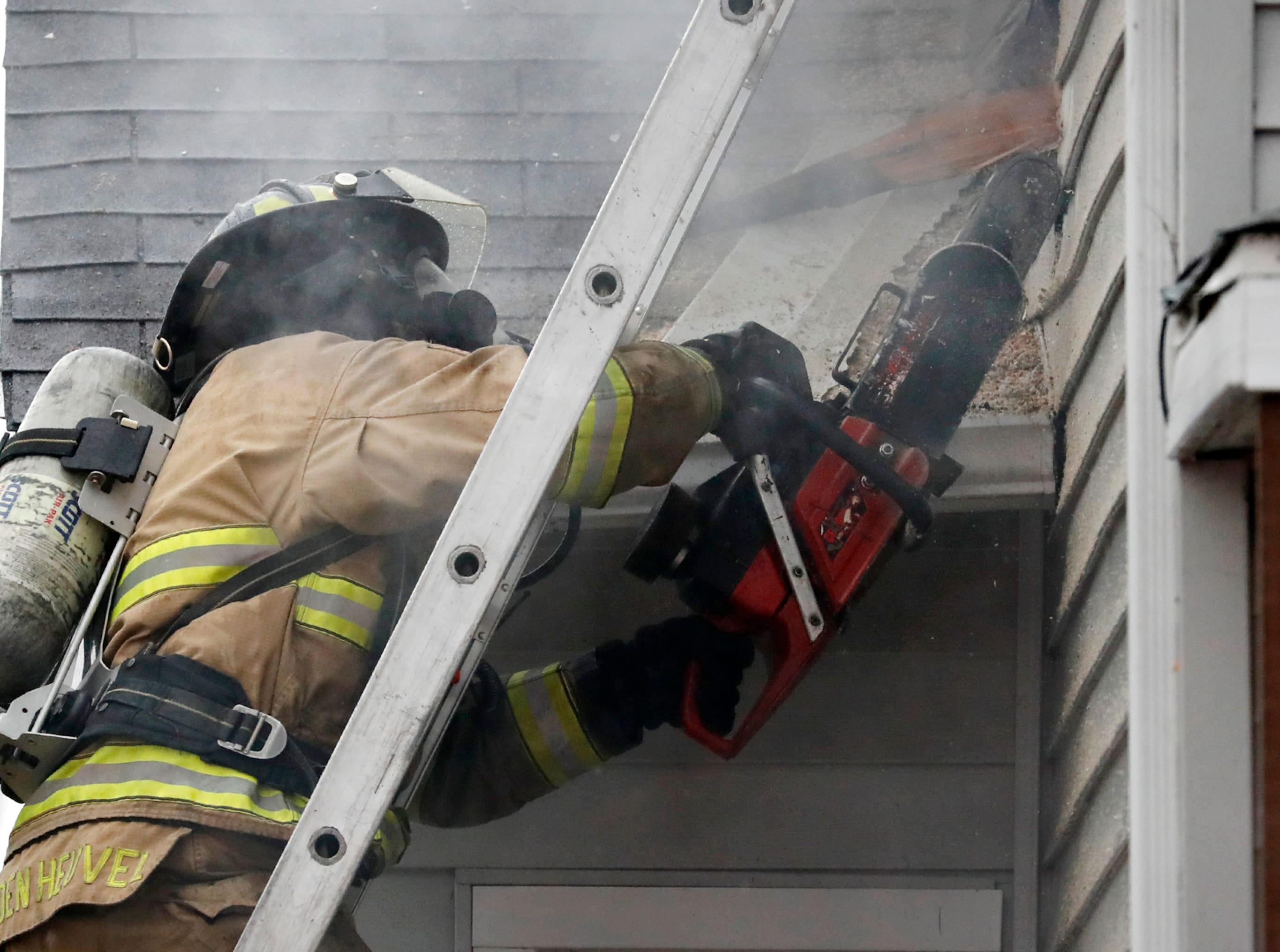 A firefighter works the scene of a structure fire on West 10th Street Thursday, Dec. 27, 2018, Kaukauna, Wis.