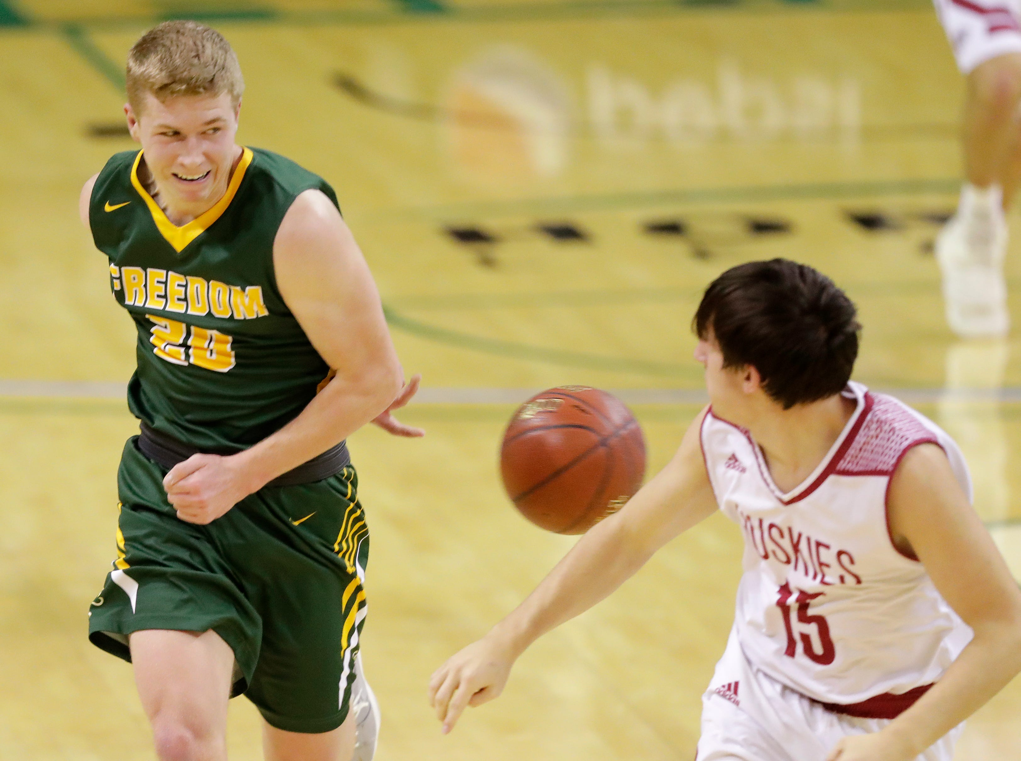 Freedom's Bryce Vandenberg (20) throws a behind the back pass against New Holstein at the Sun Drop Shootout at the Kress Center on Thursday, December 27, 2018 in Green Bay, Wis.