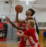 Neptune's Dwaine Jones drives in towards basket against Columbia's Connor Thompson during first half action. Neptune Boys Basketball  vs Columbia in Neptune, NJ on December 27, 2018.