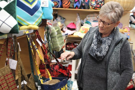 Teresa Ballard fixes some of the bags she made to sell in the Charitable Union gift shop.