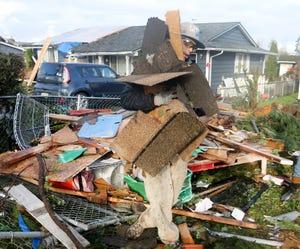 Volunteer Matthew Riley cleans up tornado damage on Dec. 27, 2018, on Serenade Way in Port Orchard.
