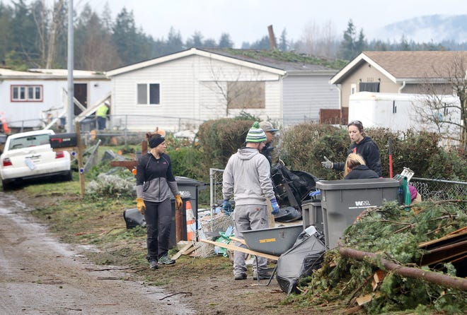 Volunteers from Westcoast Fitness in Port Orchard help clean up tornado debris last week on Serenade Way in Port Orchard.