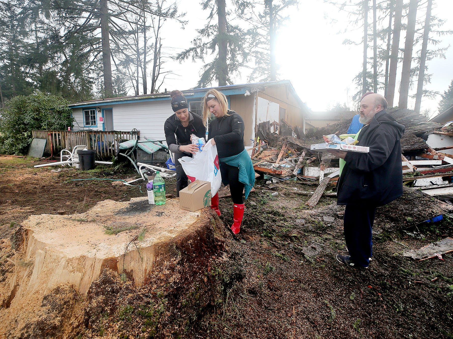 Volunteers Tiffany Cobb, center, and Terry Sulkosky from Westcoast Fitness in Port Orchard, deliver pizza, coffee, and snacks to tornado victim Chris Blake, right, on Thursday, December, 27, 2018. Blake's home in the background, on Serenade Way in Port Orchard was damaged, and he lost some big trees.