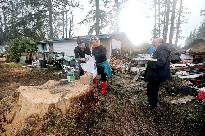 Volunteers Tiffany Cobb, center, and Terry Sulkosky from Westcoast Fitness in Port Orchard, deliver pizza, coffee, and snacks to tornado victim Chris Blake, right, on Thursday. Blake's home (in the background) on Serenade Way in Port Orchard was damaged in the Dec. 18 tornado.
