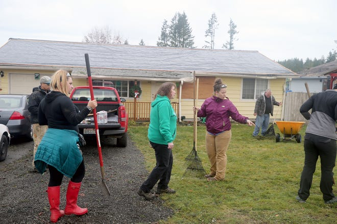 Volunteers from Westcoast Fitness worked at the home of Tonya Pettit, center, on Serenade Way in Port Orchard last week.