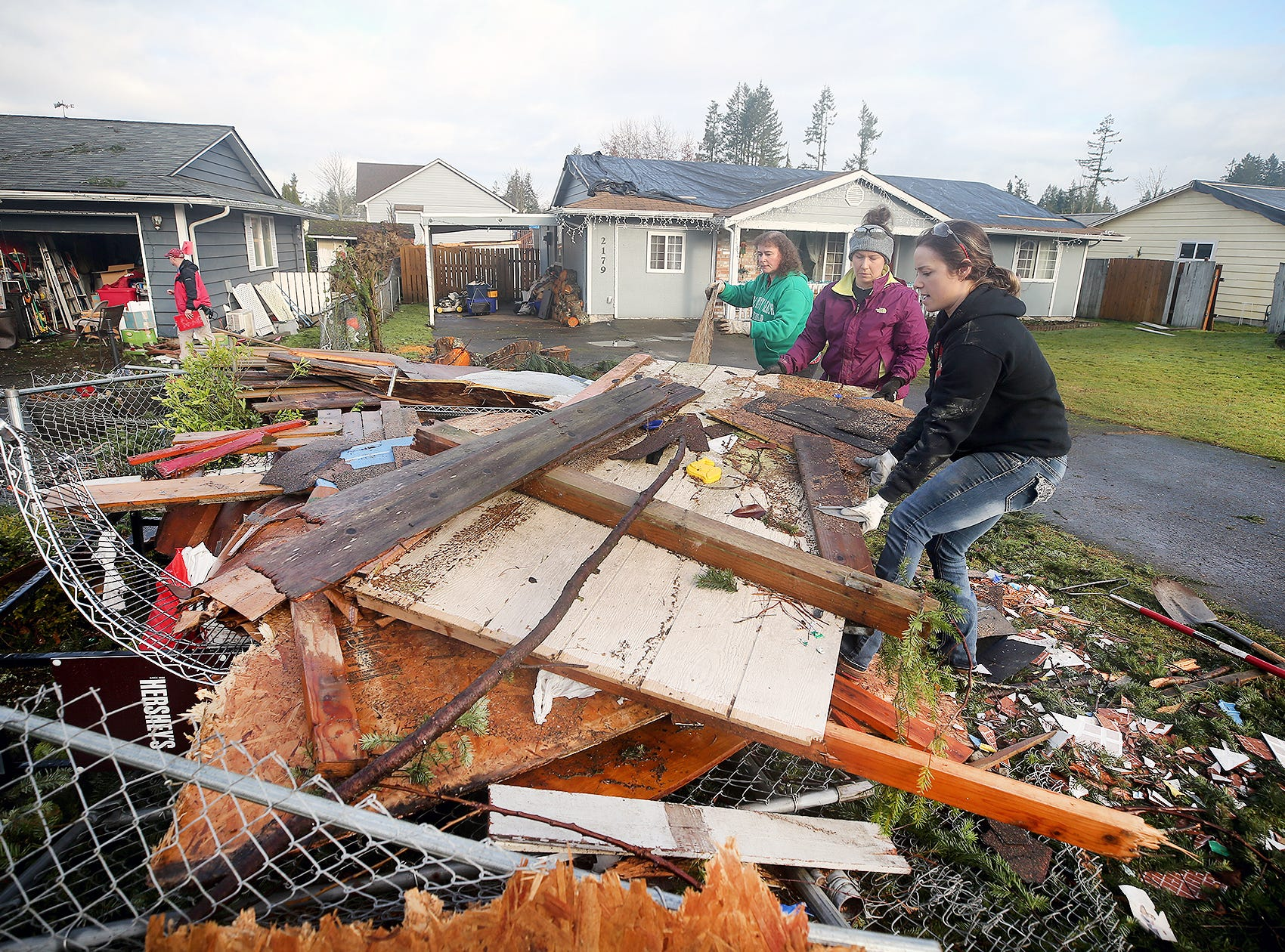 Volunteers Hollie Santos, right, and Sarah Kanyer, center, from Westcoast Fitness in Port Orchard, remove tornado debris on Thursday, December, 27, 2018, on Serenade Way in Port Orchard, Tornado victim Tonya Pettit, background in green, is helping her neighbors house she lives in the yellow hose on the far right, which was damaged.